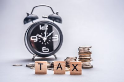 clock and coins with blocks spelling tax